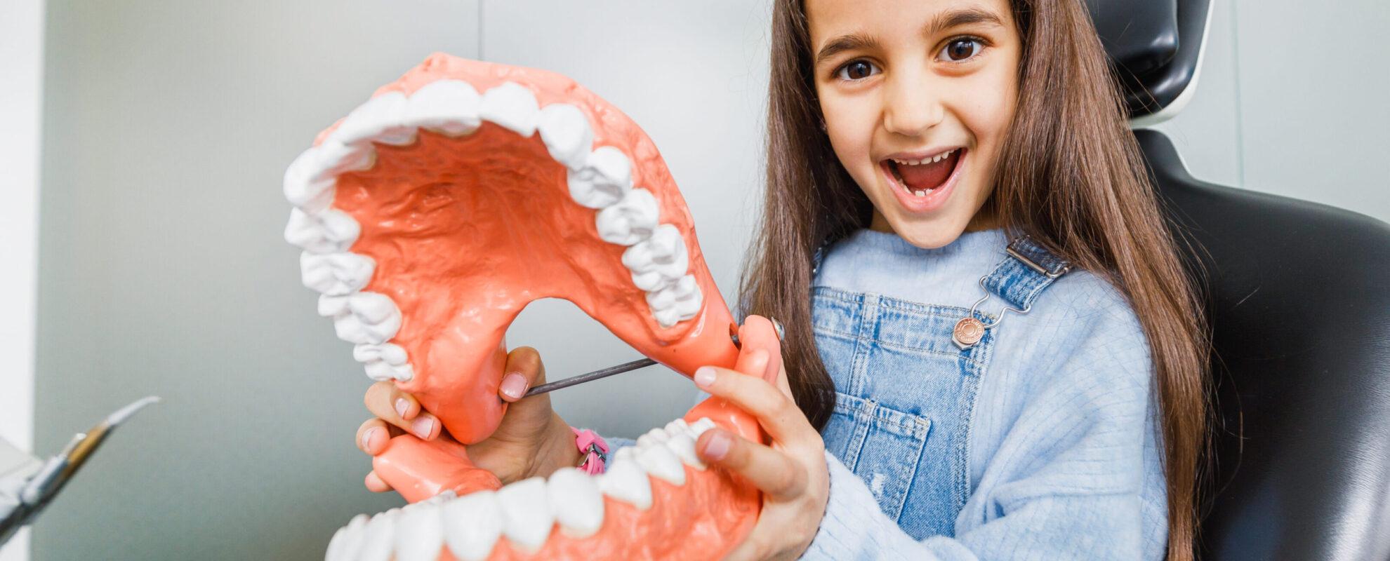 Junges Mädchen hält begeistert ein großes Modell eines Mundes