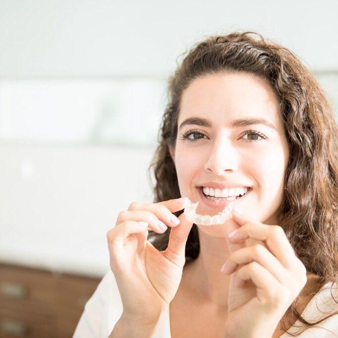 Portrait einer lachenden Frau, die eine transparente Zahnspange hält