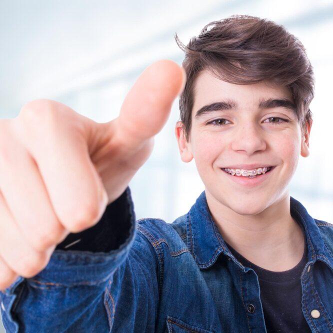 Lachender Junge mit Zahnspange zeigt einen Daumen hoch