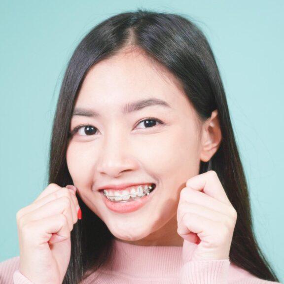 Junges Mädchen trägt eine Zahnspange und lacht