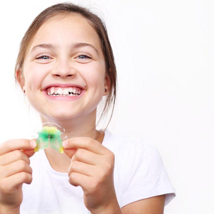 Ein lachendes Kind, das eine Zahnspange hält